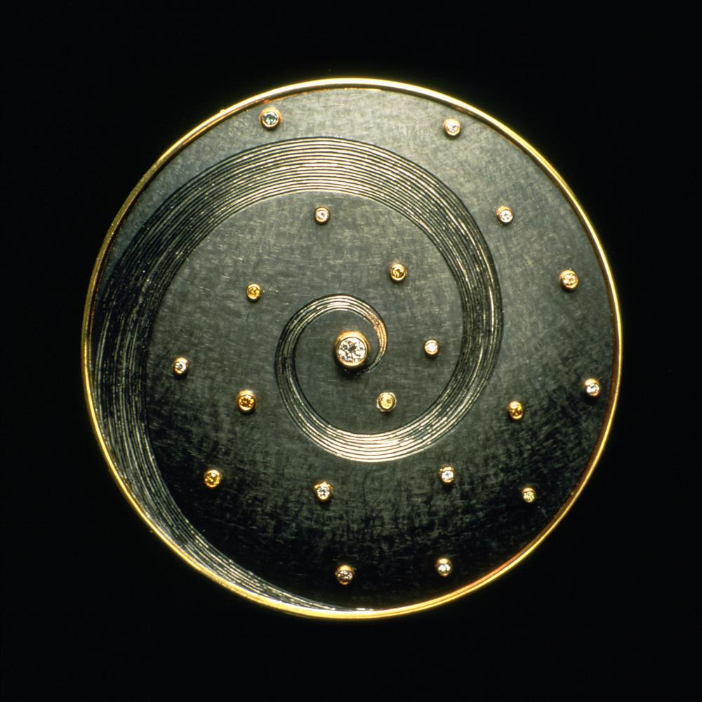 "<a href=""/jewellery/mandala-brooch-oxidised-silver-some-rhodium-plating-18ct-yellow-gold-set-white-and"">Mandala Brooch, oxidised silver, some rhodium plating, 18ct yellow gold, set with white and coloured diamonds. 6cm diameter. Photo: Geoffrey Onyett</a>"