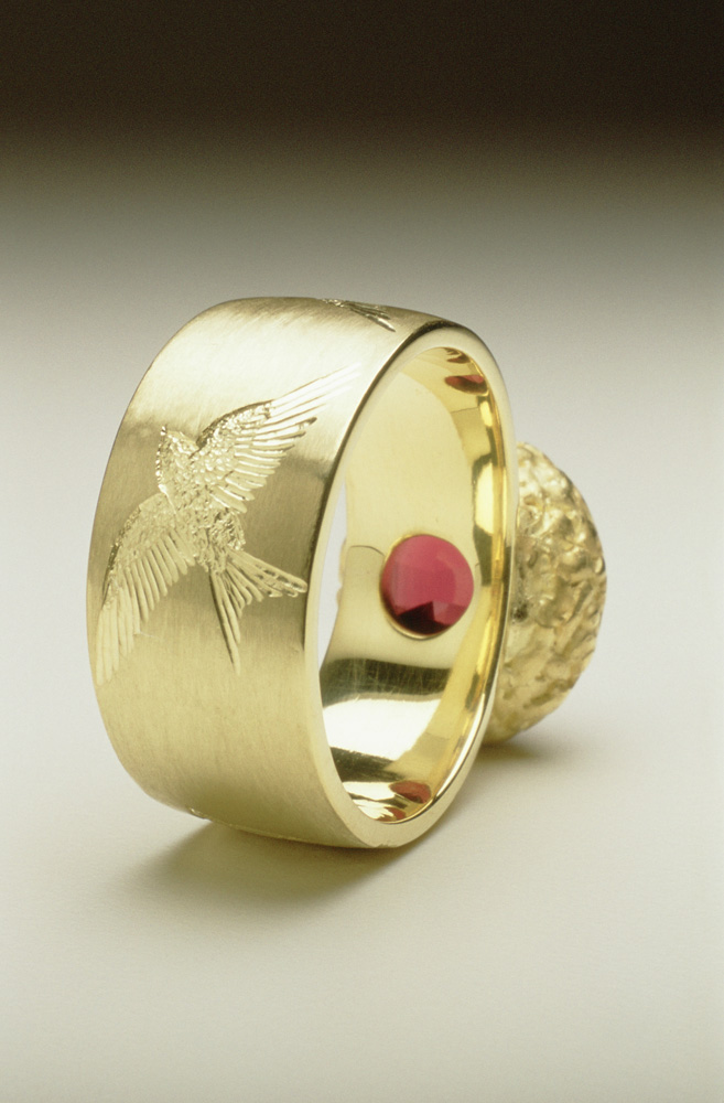"""<a href=""""/jewellery/reverse-detail-house-martin-ring-18ct-green-gold-hand-engraved-oval-chequerboard-cut"""">Reverse detail: &#039;House Martin&#039; Ring, 18ct green gold, hand engraved, oval chequerboard cut garnet.</a>"""