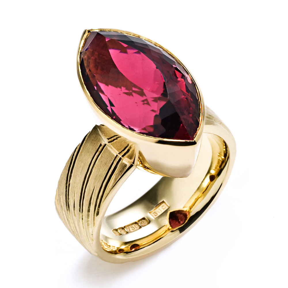 """<a href=""""/jewellery/ring-10"""">Dress Ring, 2008. 18 ct gold, shank engraved with rising sun motive. Set with marquise rubelite tourmaline. Photo : Simon Armitt</a>"""