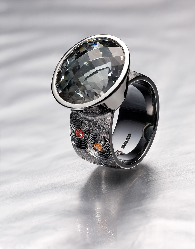 """<a href=""""/jewellery/ring-8"""">Cocktail Ring Commission 2008/9. Oval chequerboard cut grey / green Tourmaline, pink treated diamonds, silver, black rhodium plate. Photo : Simon Armitt</a>"""