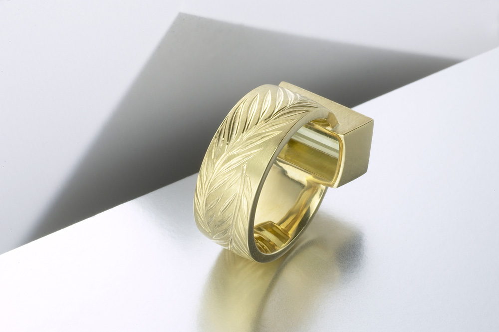 """<a href=""""/jewellery/reverse-detail-olive-ring-18ct-yellow-gold-hand-engraved-cut-interlocking-olive-branches"""">Reverse detail: &#039;Olive&#039; ring, 18ct yellow gold, hand engraved cut with interlocking olive branches, olive green tourmaline baguette. Photo: Paul Hartley</a>"""