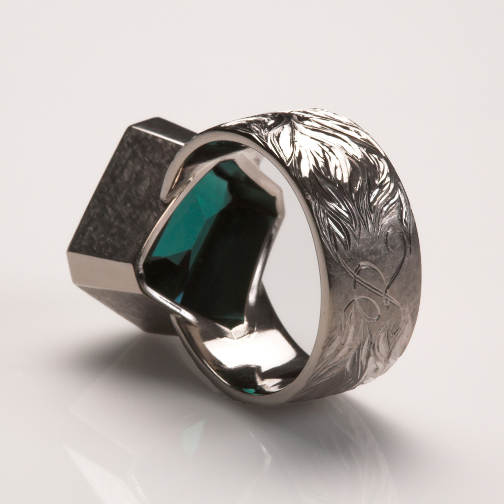 """<a href=""""/jewellery/reverse-detail-1"""">Reverse Detail: Blue Tourmaline Dress Ring set in 18ct White Gold. Ring Shank hand engraved with &#039;flame of love&#039; design radiating from initial &quot;K&quot; on the centre back of shank. Stone set diagonally on ring shank. Stone weight: 10.1 cts. Commission piece. R</a>"""