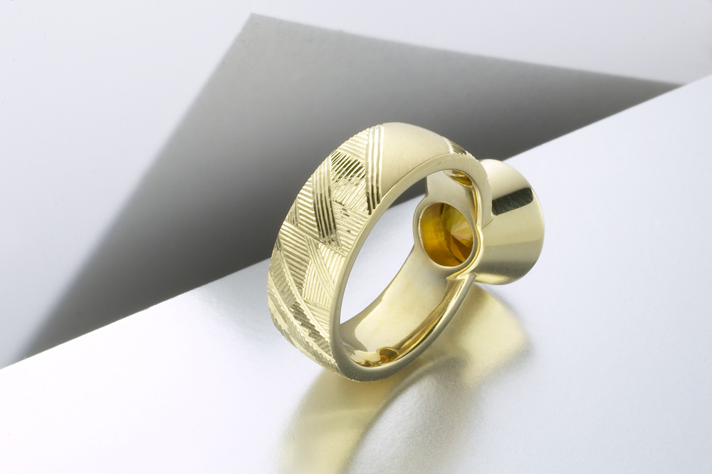 """<a href=""""/jewellery/reverse-detail-earth-dress-ring-hand-engraved-18ct-yellow-gold-brown-green-tourmaline"""">Reverse detail: &#039;Earth&#039; Dress ring, hand engraved, 18ct yellow gold, brown green tourmaline. Photo: Paul Hartley</a>"""