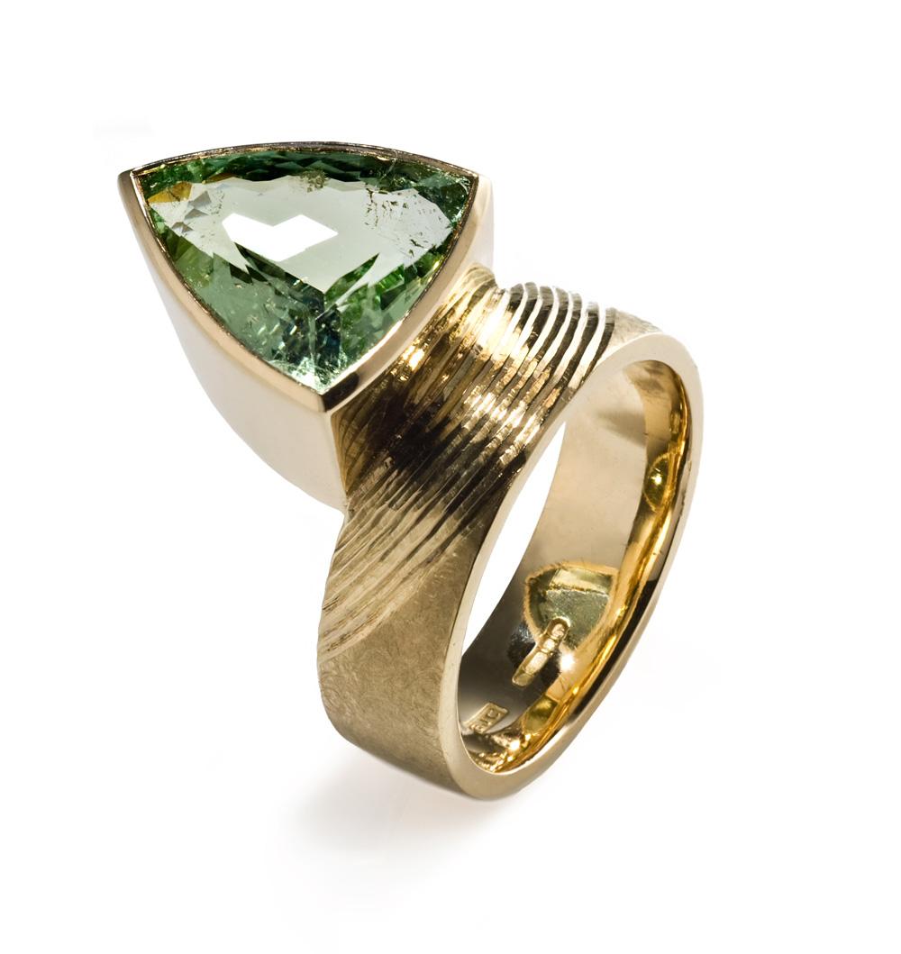 "<a href=""/jewellery/ring-2"">Dress Ring, 2008. 18 ct gold shank hand engraved, trillion cut pale green tourmaline. Photo : Simon Armitt</a>"