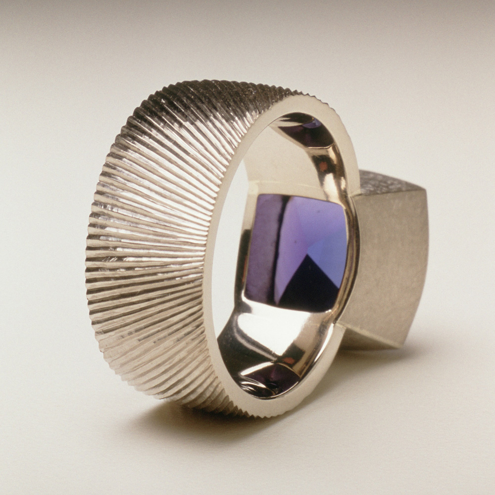 """<a href=""""/jewellery/reverse-detail-10"""">Reverse detail: Dress ring, 18ct white gold, hand engraved, cushion cut tanzanite, 7.18 cts.</a>"""