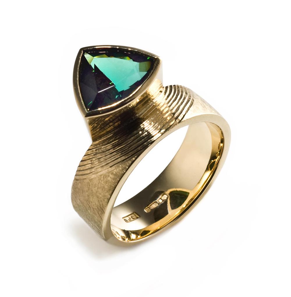 "<a href=""/jewellery/ring-0"">Dress Ring, 2008. 18 ct gold shank hand engraved, trillion cut deep green tourmaline. Photo : Simon Armitt</a>"