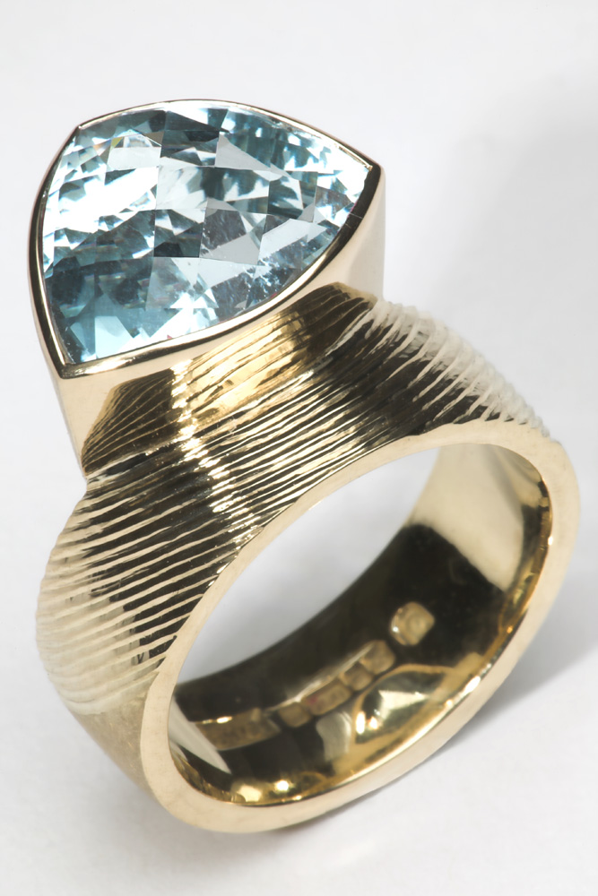 """<a href=""""/jewellery/dress-ring-18ct-yellow-gold-ring-shank-part-engraved-and-part-scrubbed-set-trillion"""">Dress Ring. 18ct yellow gold, ring shank part engraved and part scrubbed. Set with Trillion chequerboard cut Aquamarine 5.40 cts.</a>"""