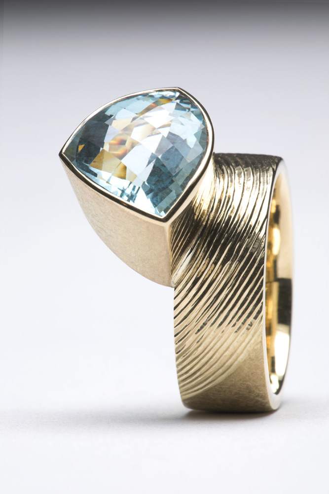 """<a href=""""/jewellery/side-detail-dress-ring-18ct-yellow-gold-ring-shank-part-engraved-and-part-scrubbed-set"""">Side detail: Dress Ring. 18ct yellow gold, ring shank part engraved and part scrubbed. Set with Trillion chequerboard cut Aquamarine 5.40 cts.</a>"""