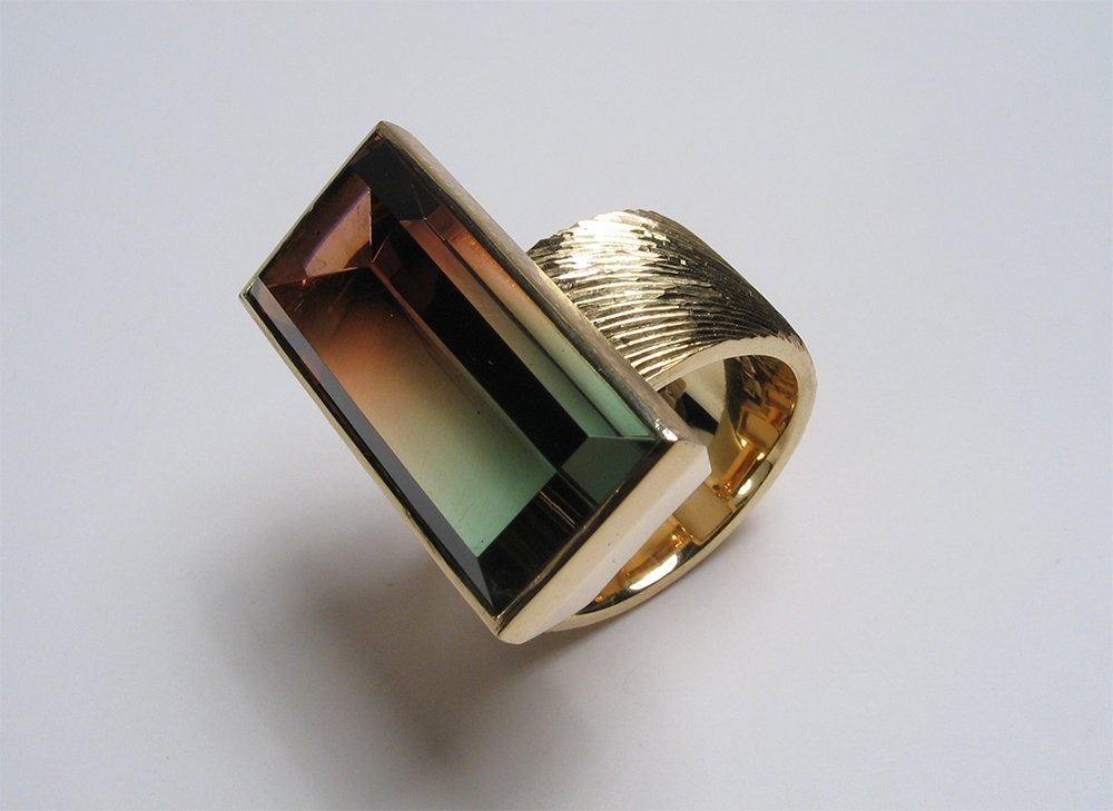 "<a href=""/jewellery/dress-ring-18ct-yellow-gold-hand-engraved-bicolour-tourmaline-photo-andra-nelki"">Dress ring, 18ct yellow gold, hand engraved, bicolour tourmaline. Photo: Andra Nelki</a>"