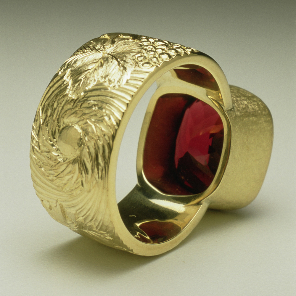 """<a href=""""/jewellery/reverse-detail-chianti-dress-ring-commission-cushion-cut-garnet-18ct-yellow-gold-hand"""">Reverse Detail: &quot;Chianti&quot; Dress Ring, Commission, cushion cut Garnet, 18ct yellow gold hand engravers and carved with vine leaves and grapes</a>"""