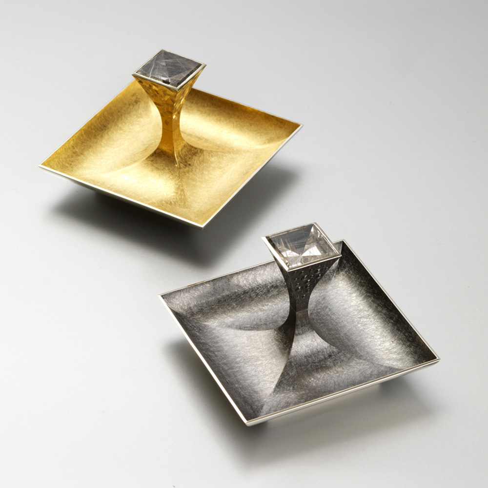 """<a href=""""/jewellery/pair-salts-13-made-silver-pinch-salt-goldsmiths-hall-spring-2009-dishes-88-mm-square"""">Pair of Salts 1/3. Made for &quot;SILVER WITH A PINCH OF SALT&quot; at Goldsmiths Hall Spring 2009. Dishes 88 mm square.. Silver yellow gilding, black rhodium plate, set with pair of square mirror cut rutilated quartz. Setting hand engraved. Photo : courtesy The Go</a>"""