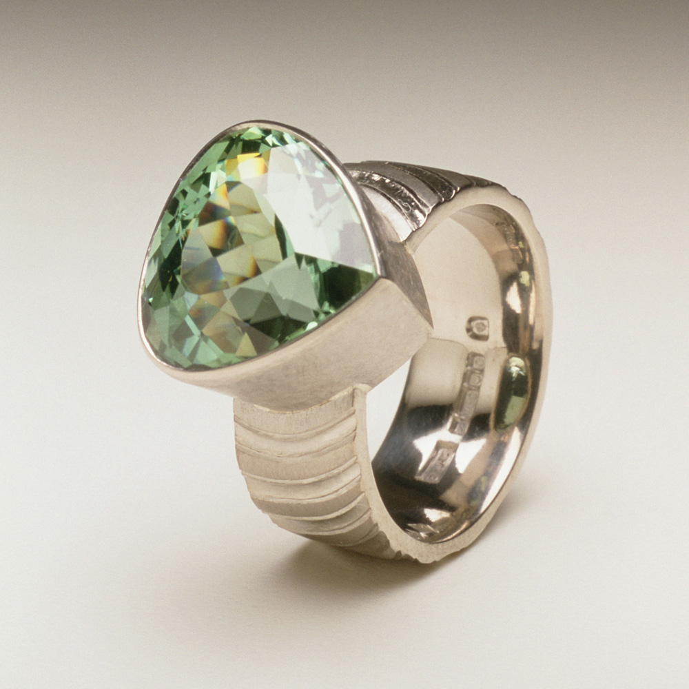 """<a href=""""/jewellery/ring-18"""">Dress ring, 18ct white gold, hand carved and engraved, pale green tourmaline.</a>"""