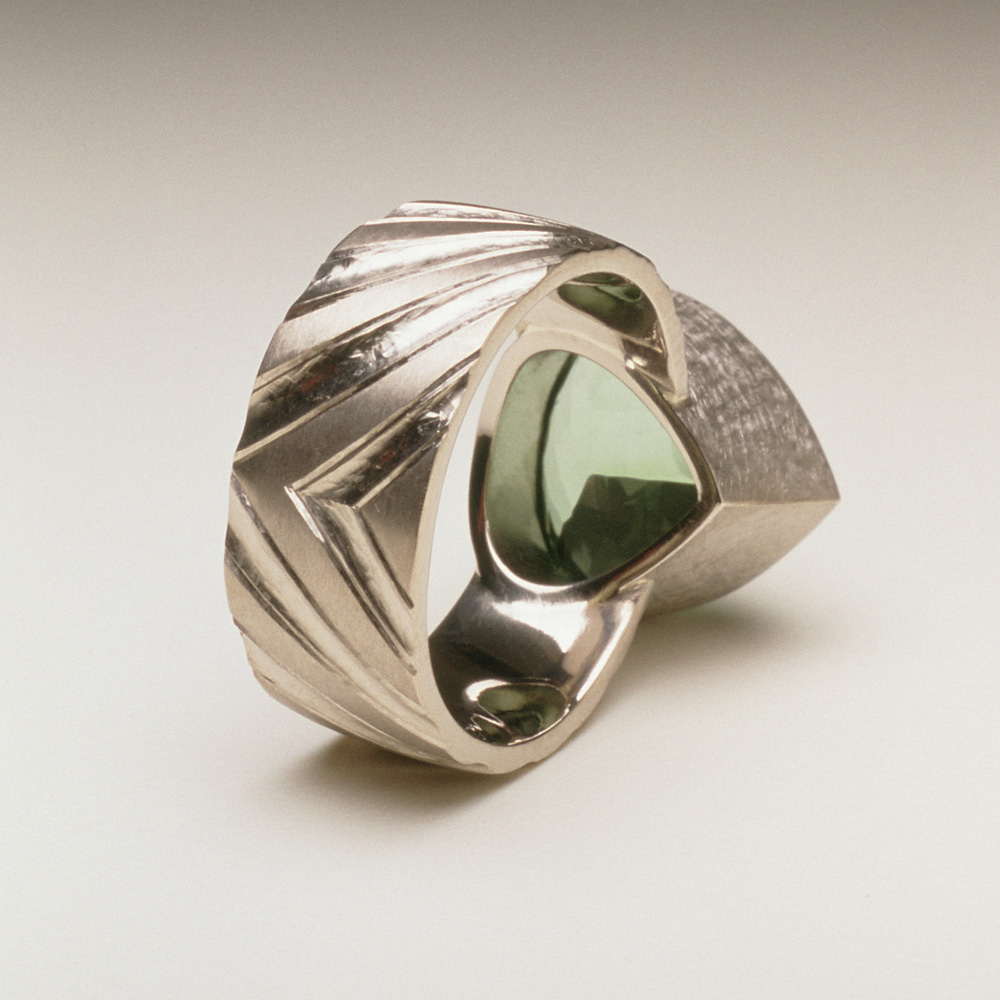 """<a href=""""/jewellery/reverse-detail-9"""">Reverse detail: Dress ring, 18ct white gold, hand carved and engraved, pale green tourmaline.</a>"""