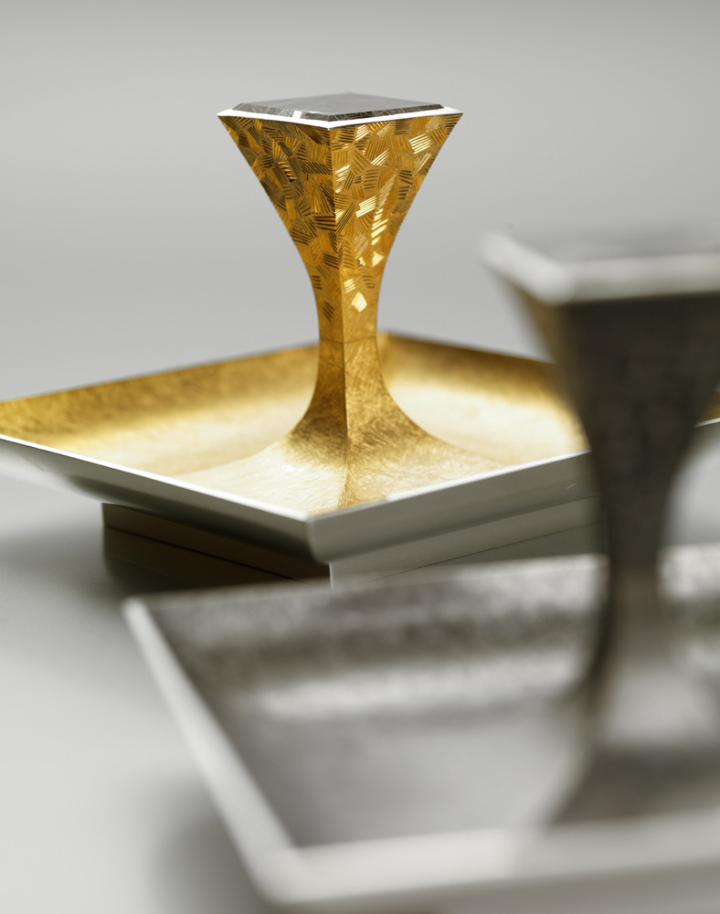 """<a href=""""/jewellery/pair-salts-23-made-silver-pinch-salt-goldsmiths-hall-spring-2009-dishes-88-mm-square"""">Pair of Salts 2/3. Made for &quot;SILVER WITH A PINCH OF SALT&quot; at Goldsmiths Hall Spring 2009. Dishes 88 mm square.. Silver yellow gilding, black rhodium plate, set with pair of square mirror cut rutilated quartz. Setting hand engraved. Photo : courtesy The Go</a>"""