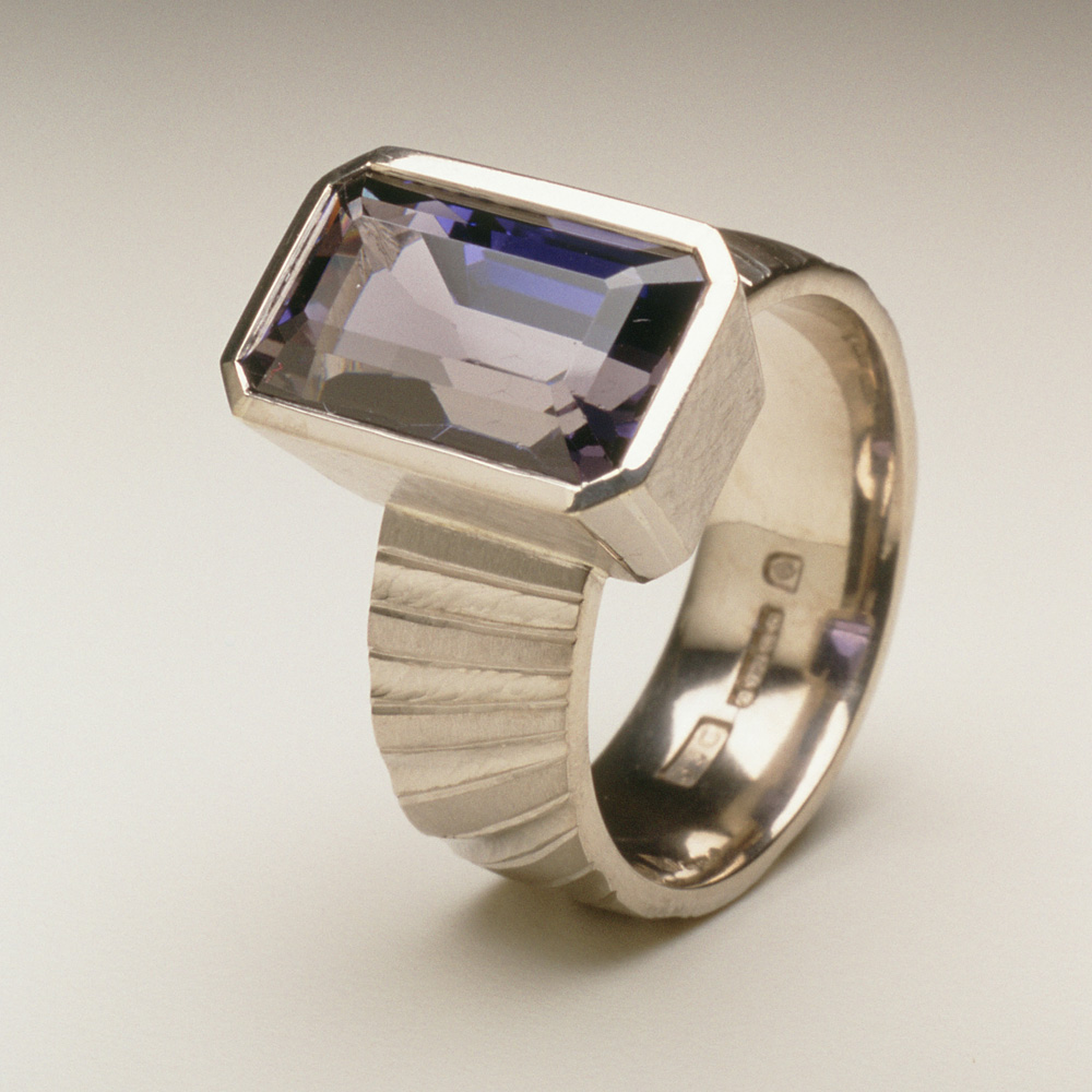 """<a href=""""/jewellery/ring-17"""">Ring shank inspired by pillars of the nave of Durham Cathedral. 18ct white gold, hand carved and engraved, setting a baguette Iolite.</a>"""