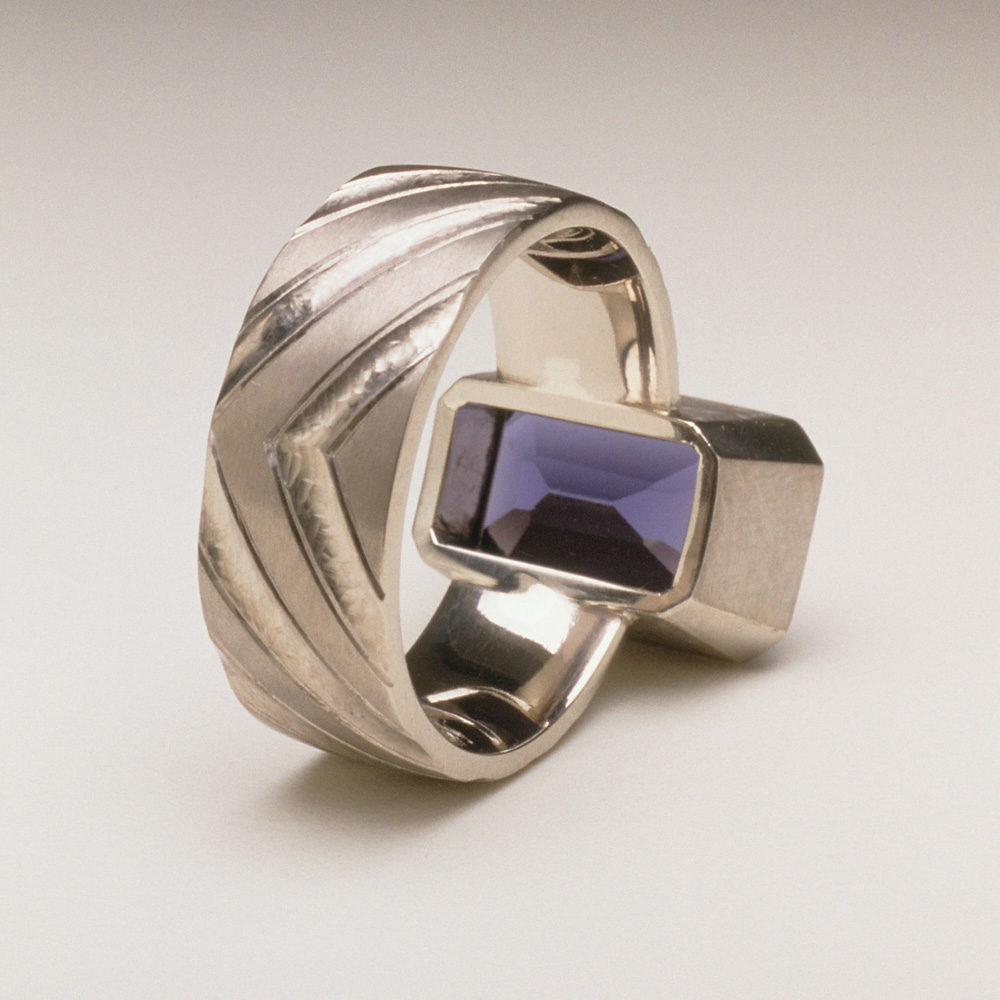 """<a href=""""/jewellery/reverse-detail-8"""">Reverse Detail: Ring shank inspired by pillars of the nave of Durham Cathedral. 18ct white gold, hand carved and engraved, setting a baguette Iolite.</a>"""