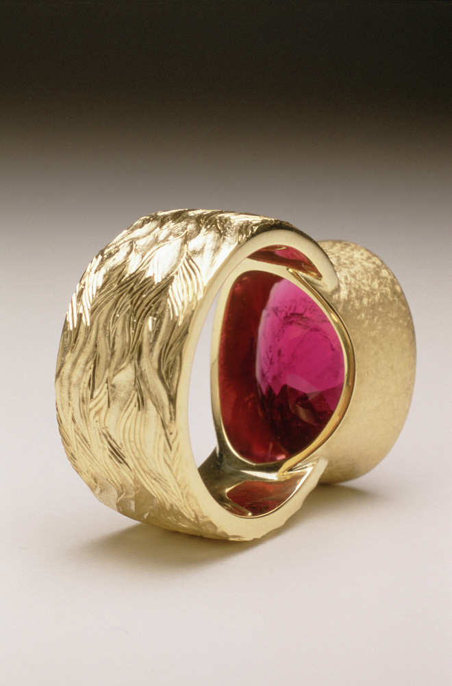 """<a href=""""/jewellery/reverse-detail-7"""">Reverse detail: &quot;Fire&quot; Dress ring, 18ct yellow gold, hand carved and engraved, red oval chequerboard rubelite tourmaline.</a>"""