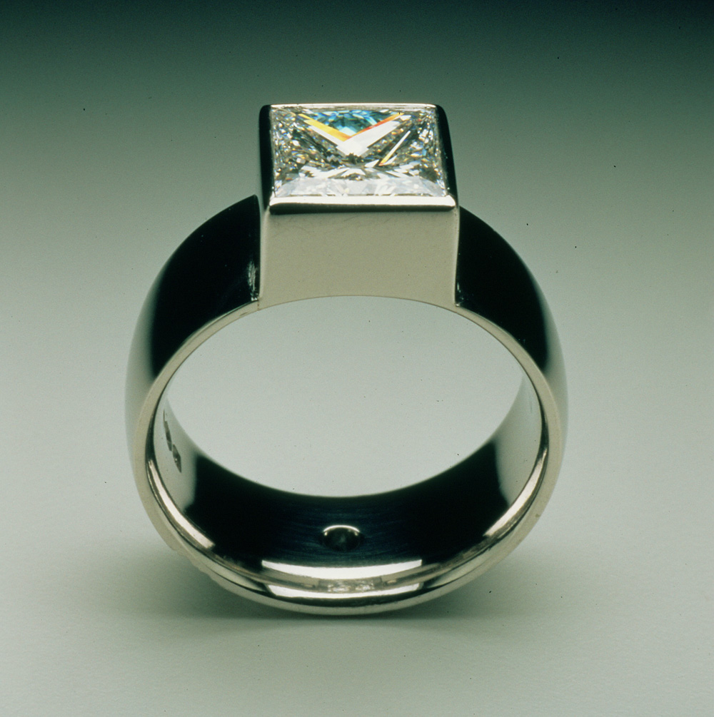 """<a href=""""/jewellery/ring-14"""">Engagement ring. Commission, square Diamond set in platinum. Small blue diamond in centre of back of the shank.</a>"""