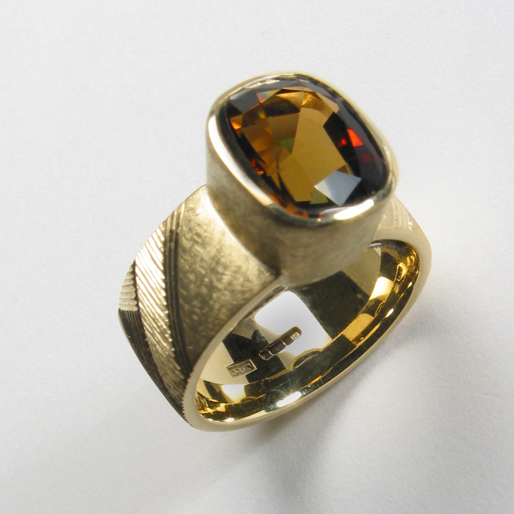 """<a href=""""/jewellery/ring-13"""">Dress ring, 18ct yellow gold, hand engraved, brown/green cushion-cut tourmaline.</a>"""