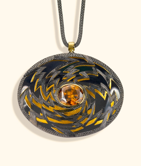 """<a href=""""/node/260"""">""""Golden Lightening"""" Oval 6cm x 4 cm. Silver hand engraved, hand pierced, mirror behind to reflect the underside.  Stone oval Zircon in orange / brown. set in 18ct gold.  View 1 Face on black reflections, White background</a>"""