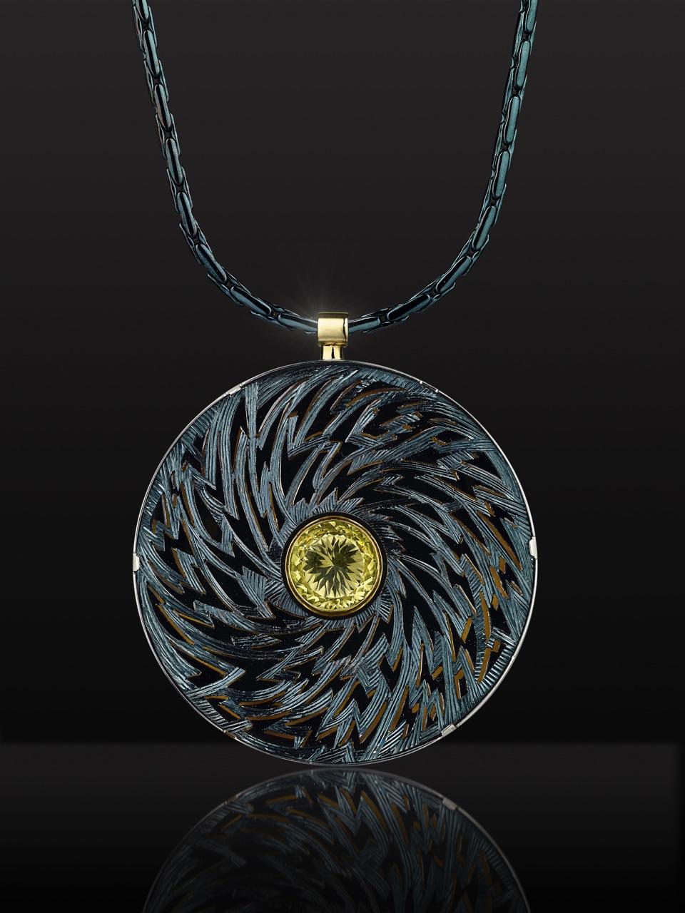 "<a href=""/node/264"">Black Lightening : Billcliffe Gallery cover photo. 6cm diameter. Silver piereced hand engraved. Finished in Bliue / Black Rhodium. Centre stone Lemon Quartz.  View 1 black background.</a>"