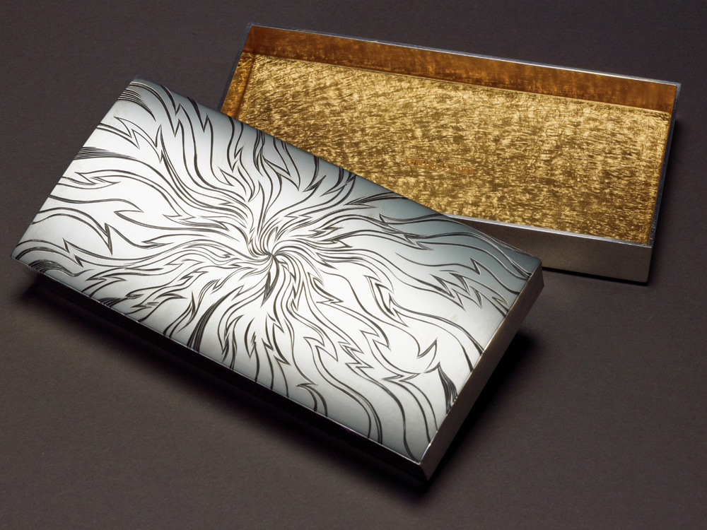 """<a href=""""/jewellery/golden-space-box-photo-12-commission-20089-size-2-x-4-x-1-silver-black-and-yellow-gilding"""">GOLDEN SPACE BOX photo 1/2. Commission 2008/9. Size 2&quot; x 4&quot; x 1&quot; Silver, Black and Yellow Gilding. Hand engraved. Photo: Simon B Armitt</a>"""