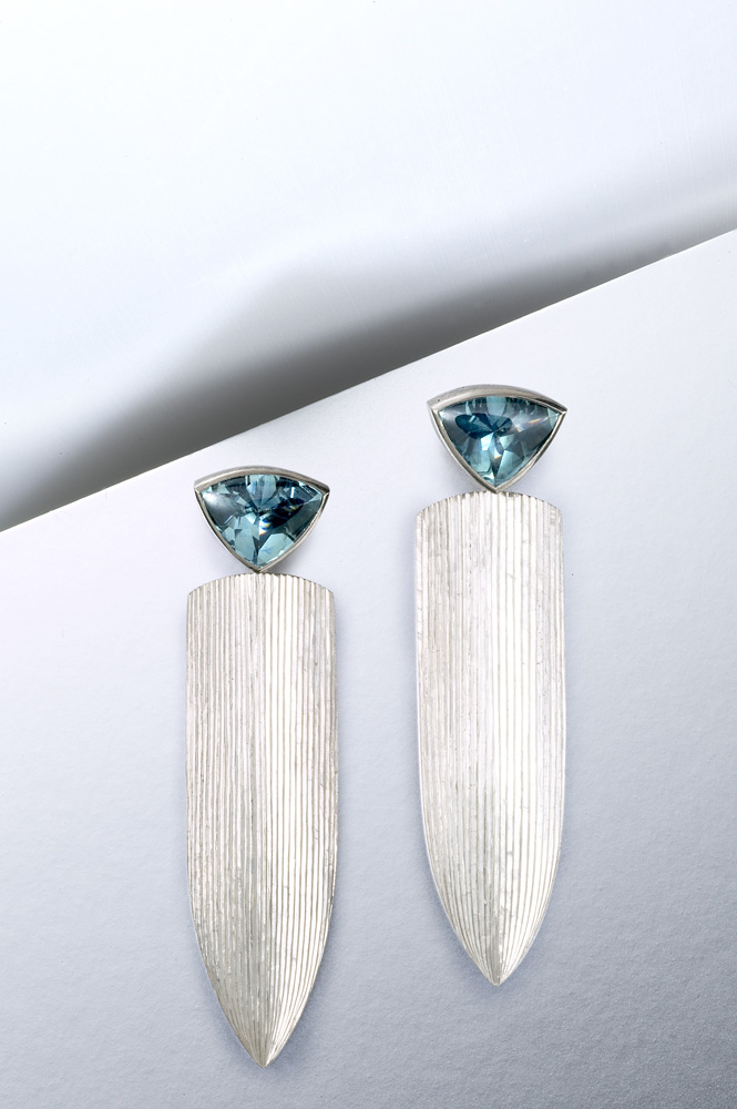 """<a href=""""/jewellery/drop-earrings-18ct-white-gold-hand-engraved-set-trillion-buff-top-montana-sapphires-40mm"""">Drop Earrings, 18ct white gold, hand engraved, set with trillion &#039;buff top&#039; Montana sapphires, 40mm. Photo: Paul Hartley</a>"""