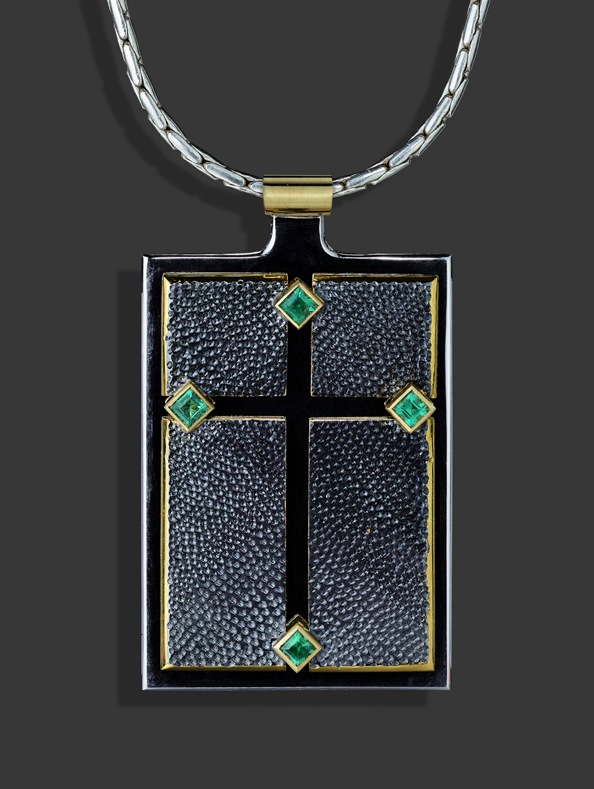 """<a href=""""/node/299"""">Emerald Cross / Silver / 18ct gold / 4 Emeralds / Gilding / Rhodium plate. The """"Cross"""" we see is actually empty space and therefore is """"nothing"""" as opposed to the """"something"""" of the four textured top panels. Photo : Simon B Armitt.</a>"""