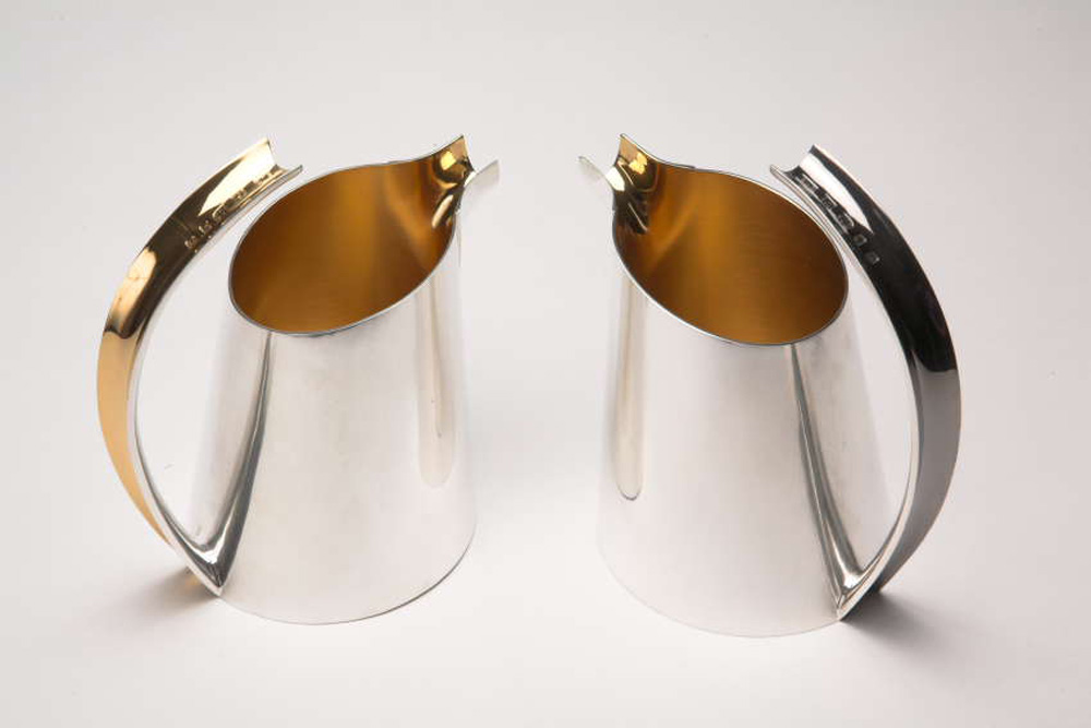 """<a href=""""/jewellery/pair-creamer-jugs-sterling-silver-yellow-and-black-gilding-hallmark-handle-ht-top-handle"""">PAIR OF CREAMER JUGS. Sterling silver. Yellow and black Gilding. Hallmark on handle. Ht. to top of handle 12.5 cm, diam. of base 8.0 cm. </a>"""