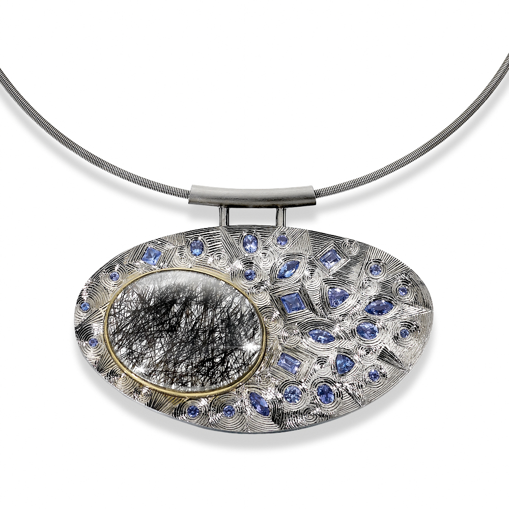"""<a href=""""/jewellery/silver-finished-grey-rhodium-hand-engraved-set-various-shaped-tanzanites-and-one-oval"""">Silver finished in grey Rhodium. Hand engraved. Set with various shaped Tanzanites and one oval Rutilated Quartz set in yellow gold. Stainless steel chain. Photo: Simon B Armitt.</a>"""
