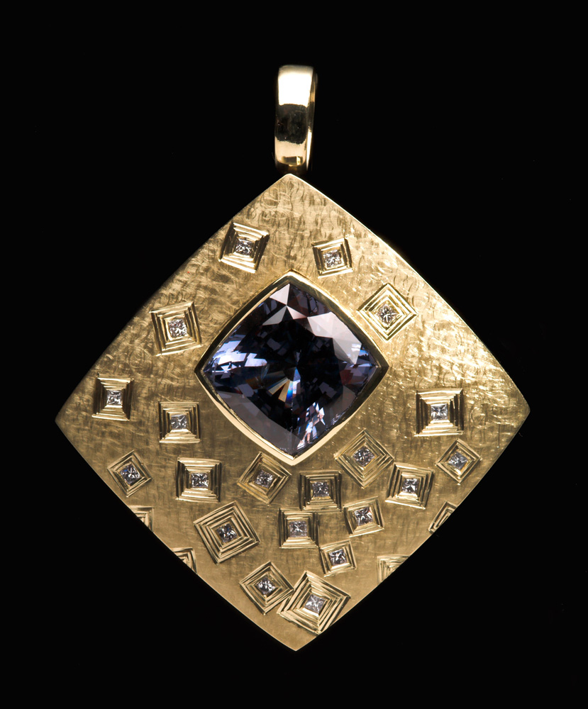 "<a href=""/jewellery/pendant-commission-18ct-green-gold-set-princess-cut-diamonds-main-stone-cushion-cut"">Pendant Commission. 18ct green gold set with princess cut diamonds, main stone cushion cut charcoal / violet Spinel. Hand engraved. 4.0 cm wide x 4.8cm ht. Photo Simon Armitt.</a>"
