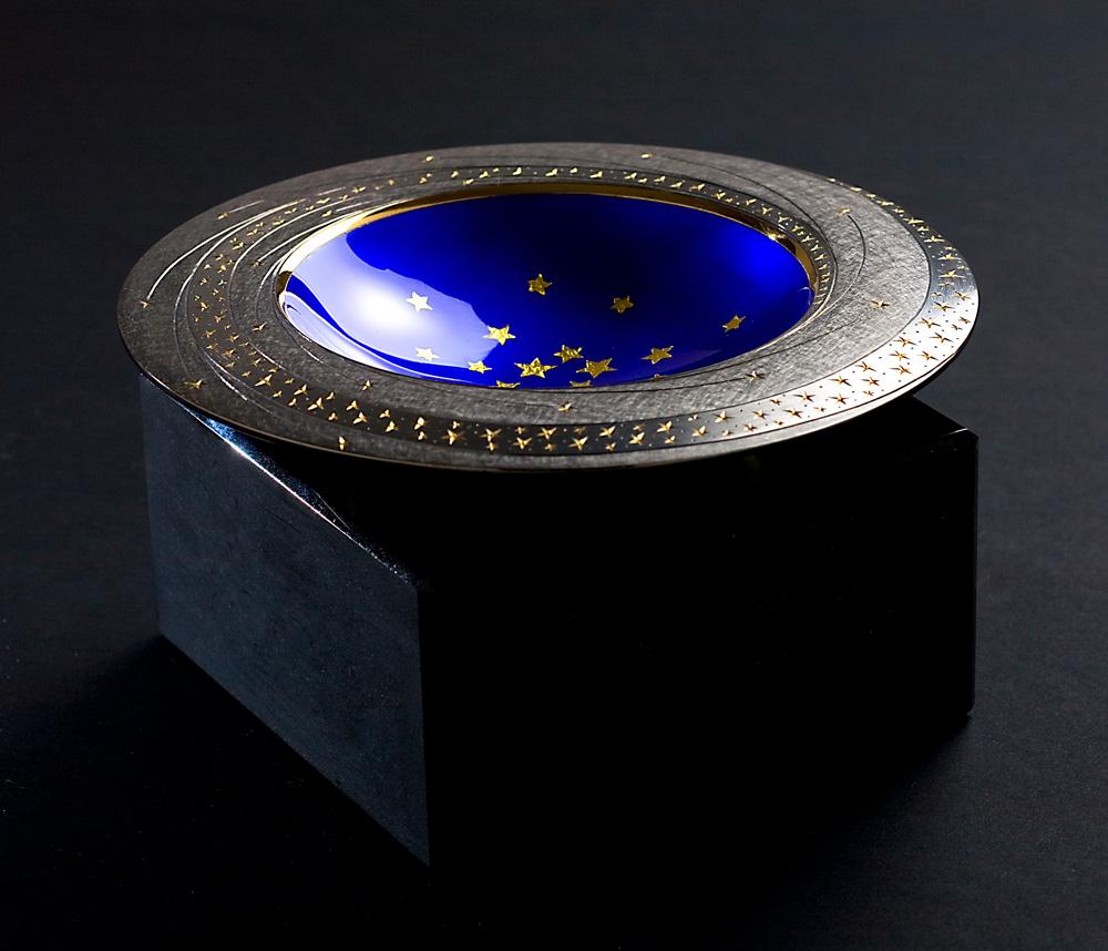 "<a href=""/jewellery/angle-view-star-bowl-20089-150-mm-diameter-base-black-obsidian-bowl-silver-yellow-and"">Angle view Star Bowl 2008/9. 150 mm diameter. Base Black Obsidian. Bowl - Silver, yellow and black gilding, hand engraved, blue enamel, gold leaf stars. Photo : Simon Armitt.</a>"