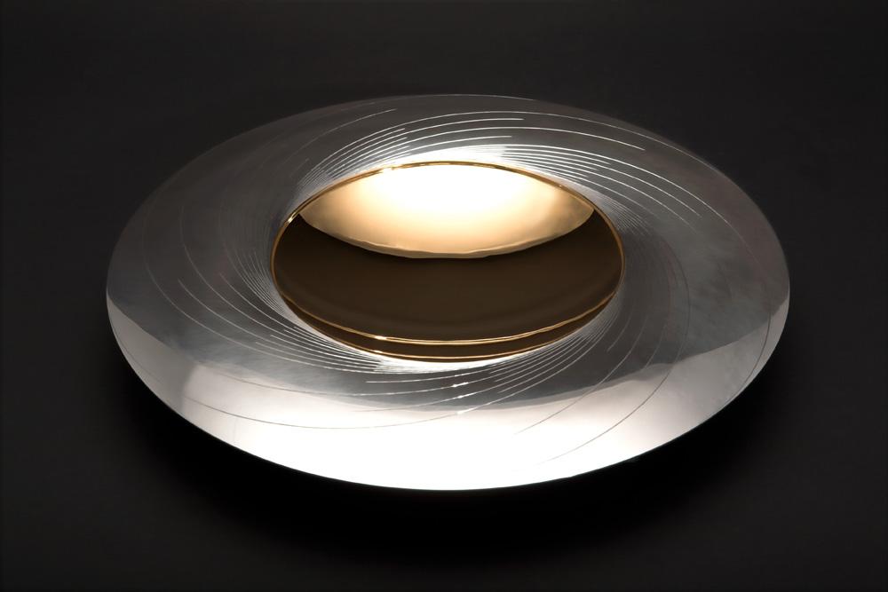 "<a href=""/jewellery/angle-view-sun-dish-300-mm-diam-silver-hand-engraved-center-yellow-gilded-stone-base"">Angle view: &quot;SUN DISH&quot; 300 mm diam. Silver, hand engraved. Center yellow gilded. Stone Base - Optical Quartz. Photo : Simon Armitt</a>"