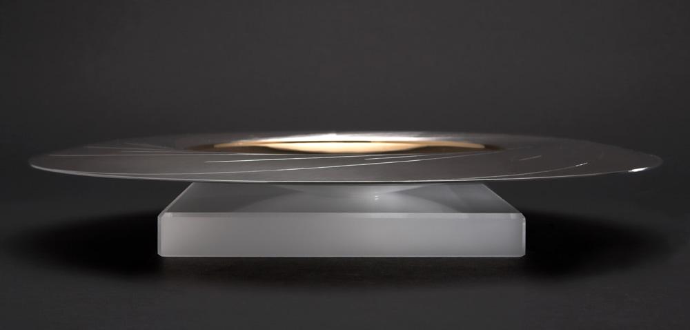 "<a href=""/jewellery/side-view-sun-dish-300-mm-diam-silver-hand-engraved-center-yellow-gilded-stone-base"">Side view: &quot;SUN DISH&quot; 300 mm diam. Silver, hand engraved. Center yellow gilded. Stone Base - Optical Quartz. Photo : Simon Armitt</a>"