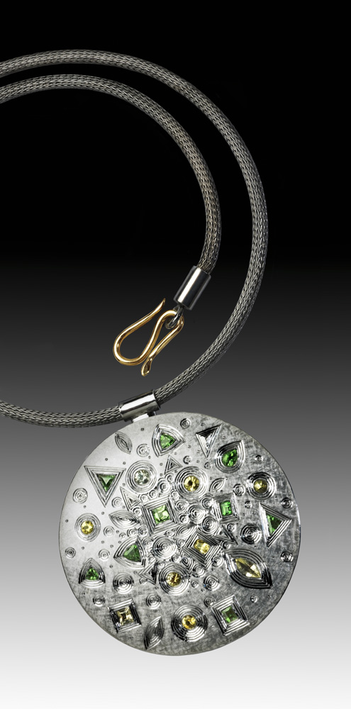"""<a href=""""/jewellery/spring-pendant-silver-hand-engraved-finished-grey-rhodium-plate-set-yellow-and-grey"""">SPRING PENDANT. Silver hand engraved, finished in grey rhodium plate. Set with yellow and grey sapphires, also green garnets. Approx 60 mm diam 2009/10. Chain also in silver, grey rhodium plated. Photo Simon B Armitt.</a>"""