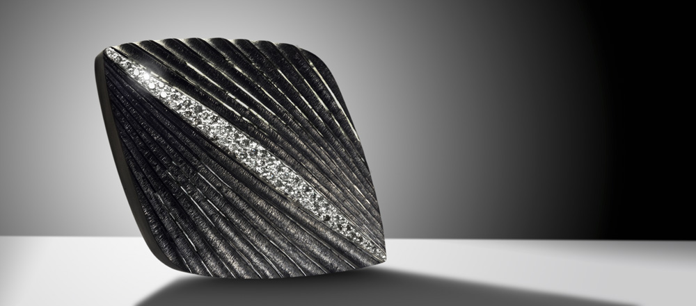 """<a href=""""/jewellery/comet-brooch-silver-hand-engraved-and-carved-finished-black-rhodium-pave-set-grey-and"""">COMET BROOCH. Silver hand engraved and carved, finished in black rhodium, pave set with grey and white diamonds. 50mm x 30mm. Photo: Simon B Armitt</a>"""