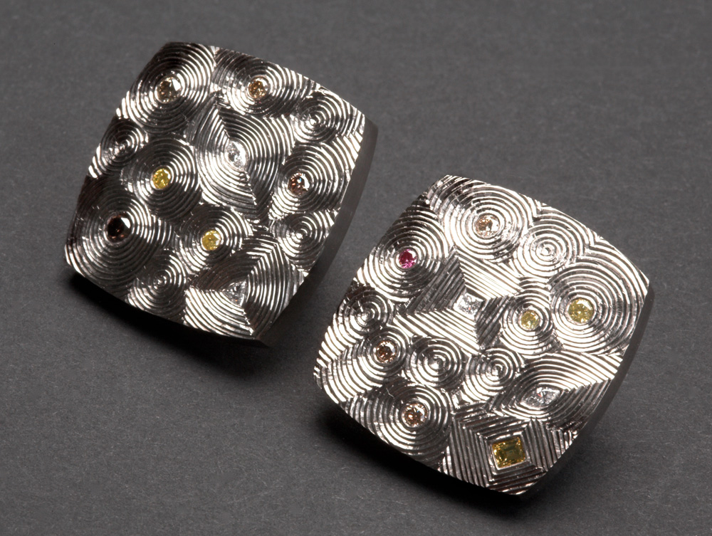 """<a href=""""/jewellery/earrings-18ct-white-gold-set-various-white-and-coloured-diamonds-clip-fittings-size-20-mm"""">Earrings 18ct White Gold set with various white and coloured Diamonds. Clip Fittings. Size 20 mm square. Photo Simon Armitt</a>"""