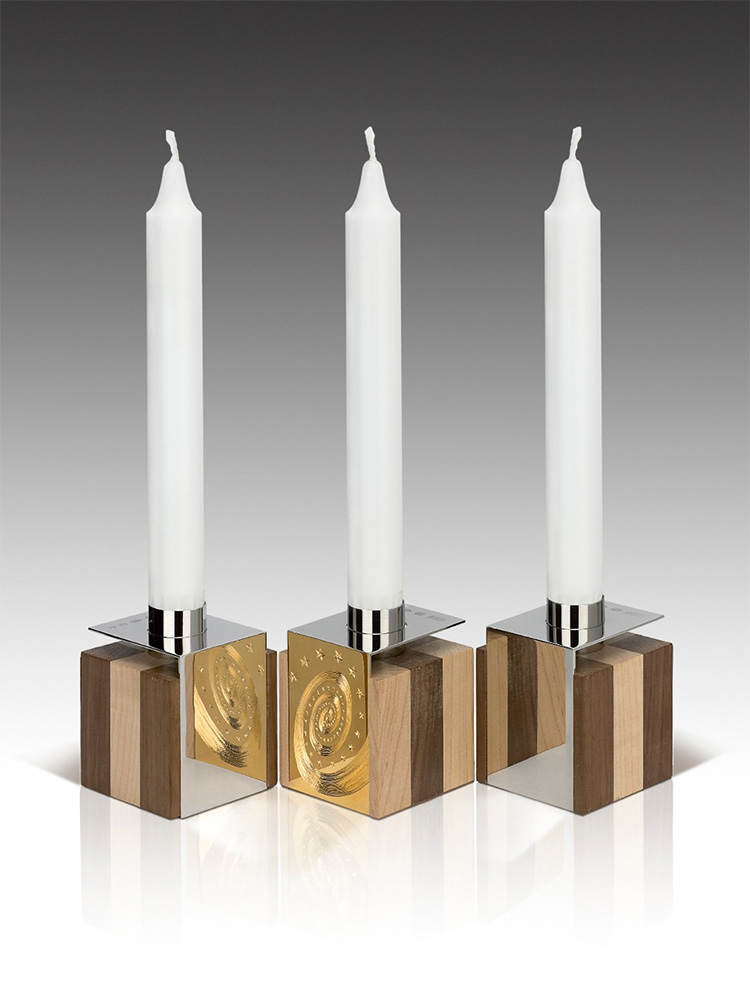 """<a href=""""/jewellery/3-candelholders-design-alan-craxford-each-cube-55cm-square-silver-finished-grey-rhodium"""">3 Candelholders Design by Alan Craxford Each cube is 5.5cm square. Silver finished in grey rhodium, part hand engraved, part gilded. Wood  English Walnut and Maple.</a>"""