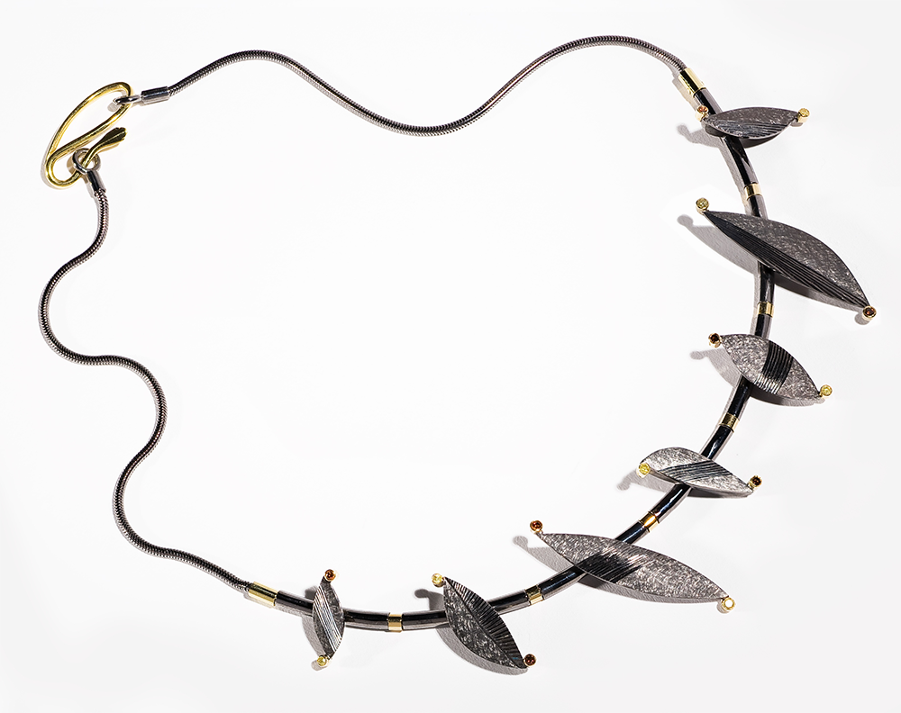 """<a href=""""/jewellery/chaos-necklace-silver-black-rhodium-plated-18-ct-gold-details-set-natural-yellow-and"""">&quot;CHAOS&quot; Necklace Silver black rhodium plated, 18 ct gold details. Set with natural yellow and treated orange diamonds. Photo : Simon Armitt.</a>"""