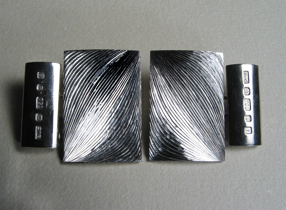 """<a href=""""/jewellery/cufflinks-18ct-white-gold-hand-engraved-face-19mm-x-25-mm-photo-andra-nelki"""">Cufflinks, 18ct white gold, hand engraved. Face: 19mm x 25 mm. Photo: Andra Nelki</a>"""