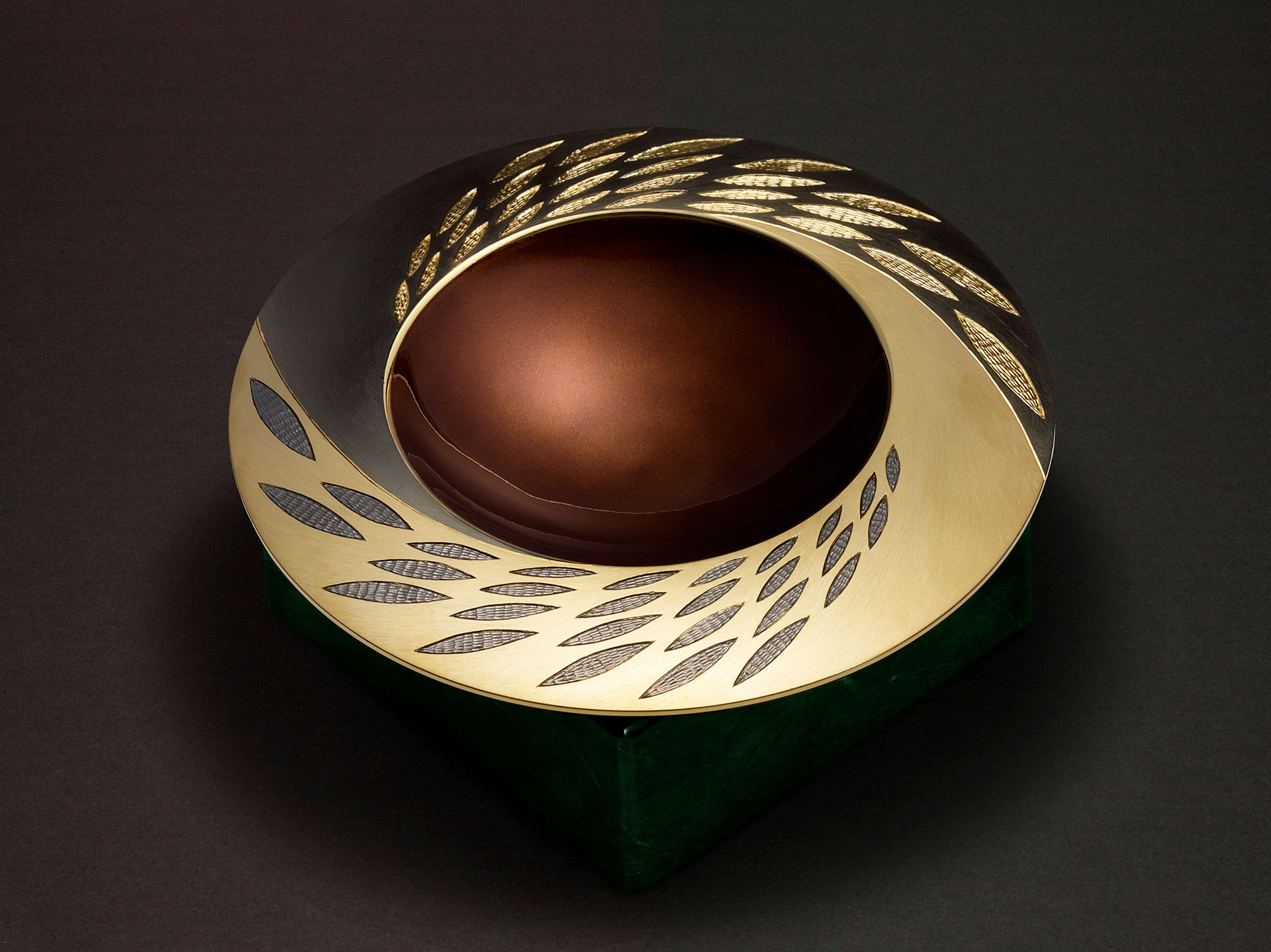 """<a href=""""/jewellery/angle-view-elements-spinning-bowl-earth-2007-reworked-2009-150mm-diameter-silver-hand"""">Angle view: ELEMENTS SPINNING BOWL - EARTH 2007 reworked 2009. 150mm diameter. Silver, hand engraved / carved, black and yellow gilding, earth/bronze/brown enamel. Base in green verdite. Photo : Simon B Armitt.</a>"""