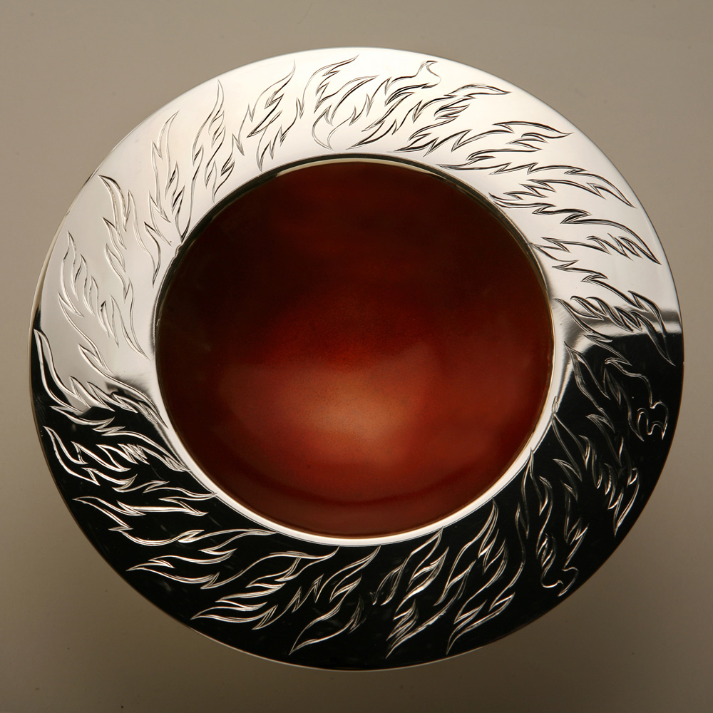 """<a href=""""/jewellery/elements-spinning-bowl-fire-150mm-diam-brittania-silver-hand-engraved-orange-enamel-photo"""">ELEMENTS SPINNING BOWL - FIRE 150mm diam. Brittania Silver, Hand Engraved, Orange enamel. Photo Andra Nelki</a>"""