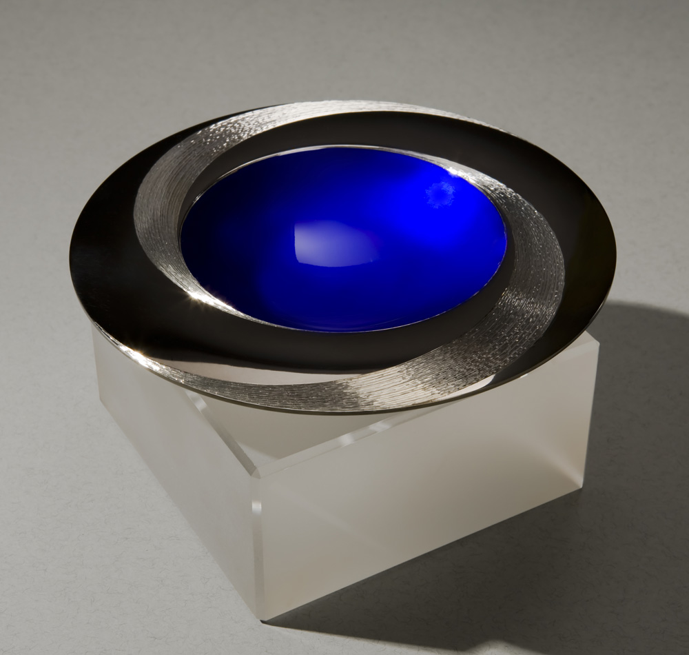 """<a href=""""/jewellery/angle-view-blue-infinity-bowl-150-mm-diameter-britannia-silver-blue-enamel-black-gilding"""">Angle view: BLUE INFINITY BOWL 150 mm diameter. Britannia Silver. Blue Enamel, Black Gilding, Hand Engraved. Base frosted and polished Optical Quartz. Bowl is designed to spin gently on its stone base. Photo : Simon Armitt</a>"""