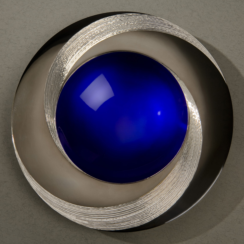 """<a href=""""/jewellery/blue-infinity-bowl-150-mm-diameter-britannia-silver-blue-enamel-black-gilding-hand-0"""">BLUE INFINITY BOWL 150 mm diameter. Britannia Silver. Blue Enamel, Black Gilding, Hand Engraved. Base frosted and polished Optical Quartz. Bowl is designed to spin gently on its stone base. Photo : Simon Armitt</a>"""