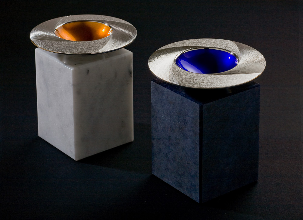 """<a href=""""/jewellery/midday-and-midnight-bowls-commission-pieces-2009-110-mm-diam-silver-hand-engraved"""">Midday and Midnight Bowls. Commission pieces 2009. 110 mm diam. Silver, hand engraved, yellow/orange and blue enamel respectively. Photo : Simon Armitt</a>"""
