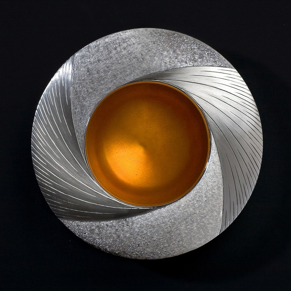 """<a href=""""/jewellery/midday-bowl-commission-piece-2009-110-mm-diam-silver-hand-engraved-yellow-orange-enamel"""">Midday Bowl Commission piece 2009. 110 mm diam. Silver, hand engraved, yellow / orange enamel. Photo : Simon Armitt</a>"""