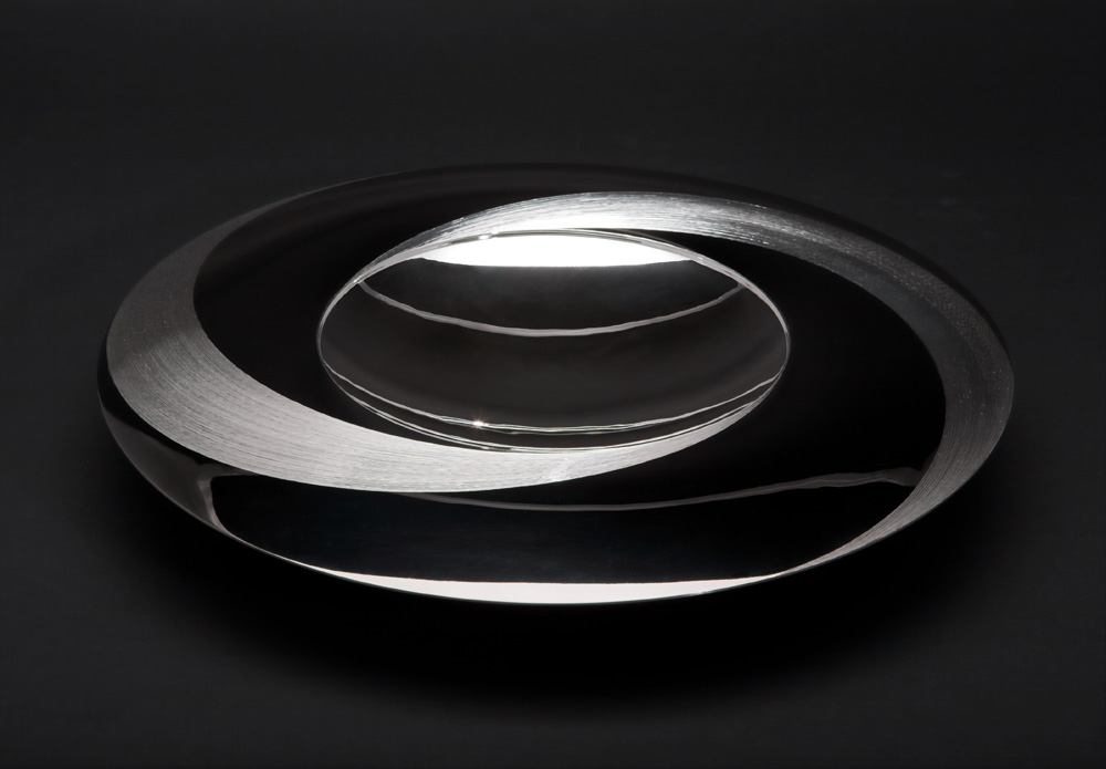 "<a href=""/jewellery/angle-view-moon-dish-300-mm-diam-silver-hand-engraved-black-gilding-stone-base-black"">Angle view: &quot;MOON DISH&quot; 300 mm diam. Silver, hand engraved, black gilding. Stone base - Black Obsidian. Photo : Simon Armitt</a>"