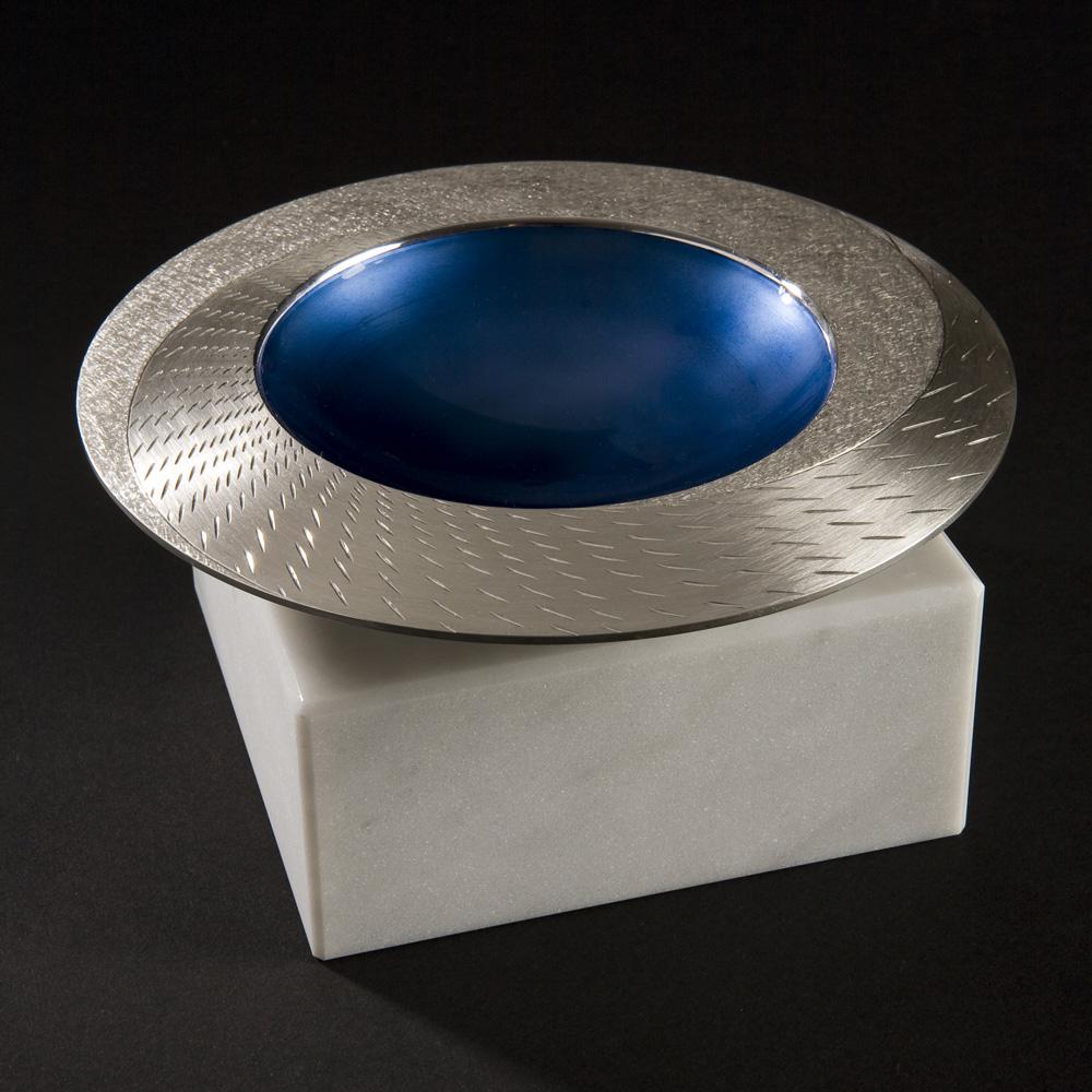 "<a href=""/jewellery/angle-view-rain-spinning-bowl-2008-150-mm-diameter-brittannia-silver-moonstone-blue-enamel"">Angle view: RAIN SPINNING BOWL 2008. 150 mm diameter. Brittannia Silver, Moonstone Blue enamel, white marble. Photo: Simon Armitt</a>"