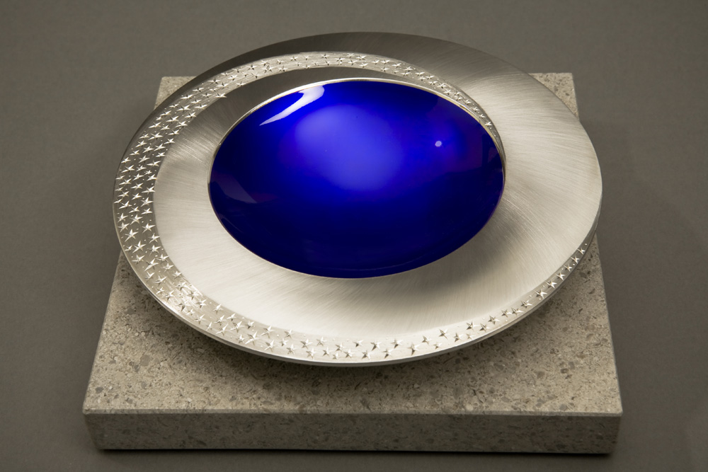 """<a href=""""/jewellery/angle-view-starlight-bowl-150-mm-diameter-britannia-silver-blue-enamel-hand-engraved"""">Angle view: STARLIGHT BOWL 150 mm diameter. Britannia Silver. Blue Enamel, Hand Engraved. Brushed and striated finish. Base polished Limestone. Bowl is designed to spin gently on its stone base. Photo : Simon Armitt</a>"""