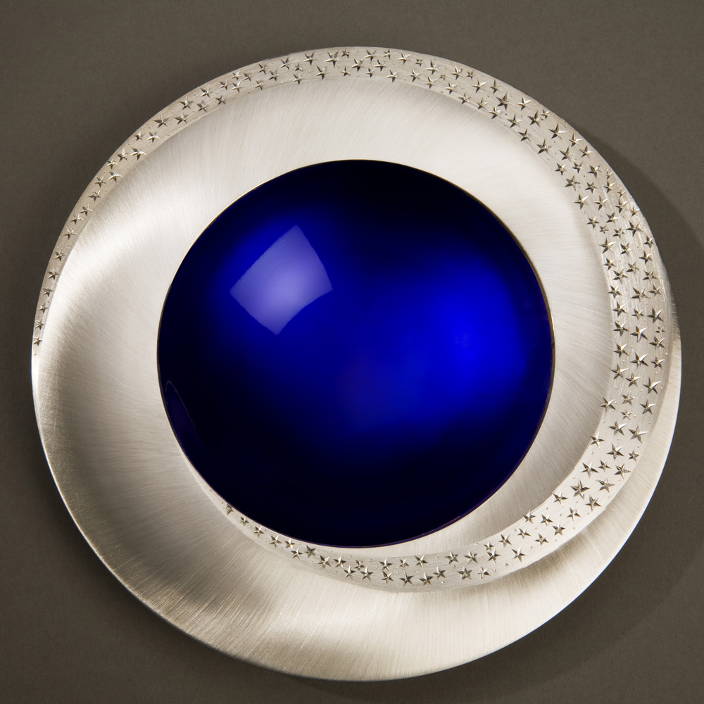 """<a href=""""/jewellery/starlight-bowl-150-mm-diameter-britannia-silver-blue-enamel-hand-engraved-brushed-and"""">STARLIGHT BOWL 150 mm diameter. Britannia Silver. Blue Enamel, Hand Engraved. Brushed and striated finish. Base polished Limestone. Bowl is designed to spin gently on its stone base. Photo : Simon Armitt</a>"""